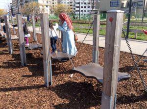 Mutter hilft ihrem Kind auf Balancegeraet im Helmut Zilk Park